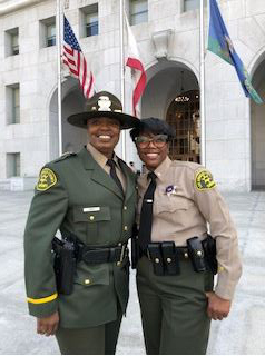 Portrait of April in class A uniform. Green jacket with gold patch, large green Smokey style hat with round wide brim and a badge on the middle. she is standing next to another deputy who is dressed in a tan and green sheriffs uniform. they are staning infront of the flag poles at the entrance of the arches in fornt of the Hall of Justice, the Sheriff's Department Headquaters.