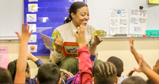 April Tardy is in Sheriff's Department Uniform, reading a book to children in a classroom.