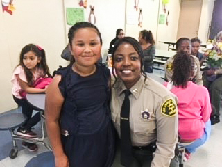 Picture of April Tardy standing next to a girl in a classroom filled with other students. April is dressed in a LA County Sheriff's Uniform.