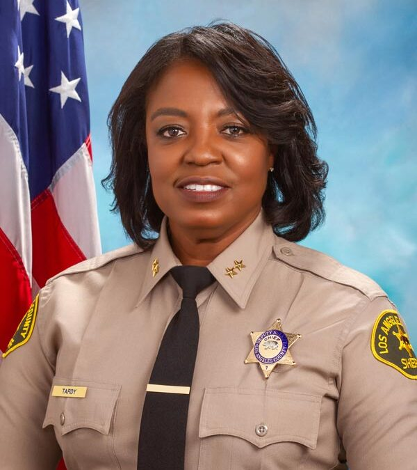 portrait of Chief April tardy. She is in uniform shown from the waist up. Wearing a tan long sleave shirt with a badge name plate black tie. There is a blue background and american flag in the background.