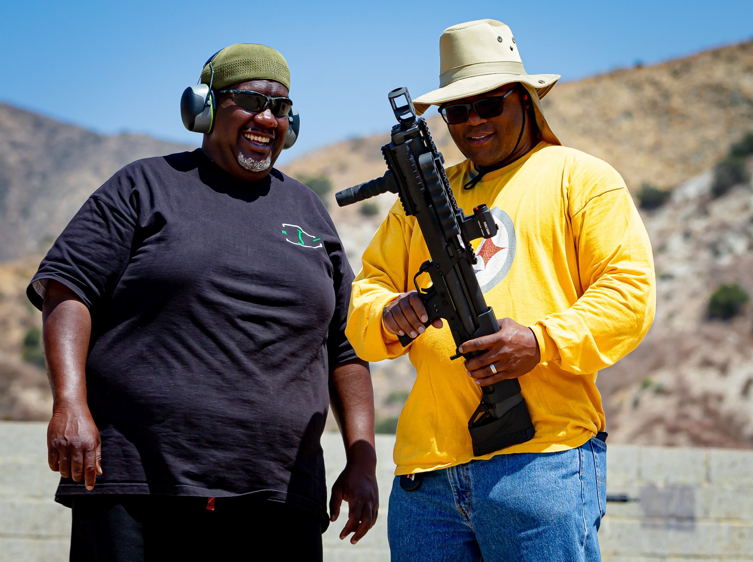 Two men are standing next to eachother looking at a Short shotgun. The man on the right is wearing hearing protection and is wearing a black shortsleeve shrit and the man on the right has a large brim green hat and a longsleeve yellow shirt.