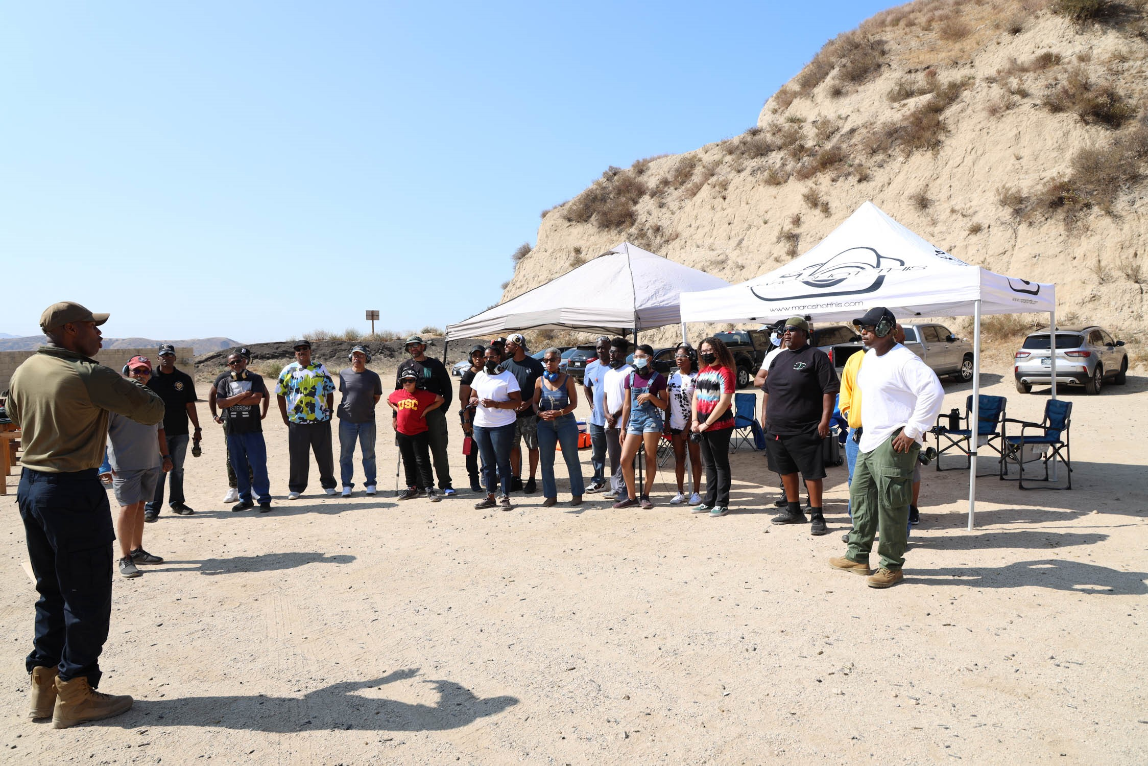A group of over 30 individuals are standing in the desert with a ridge in the background there are various tables and two easy up tents set up.