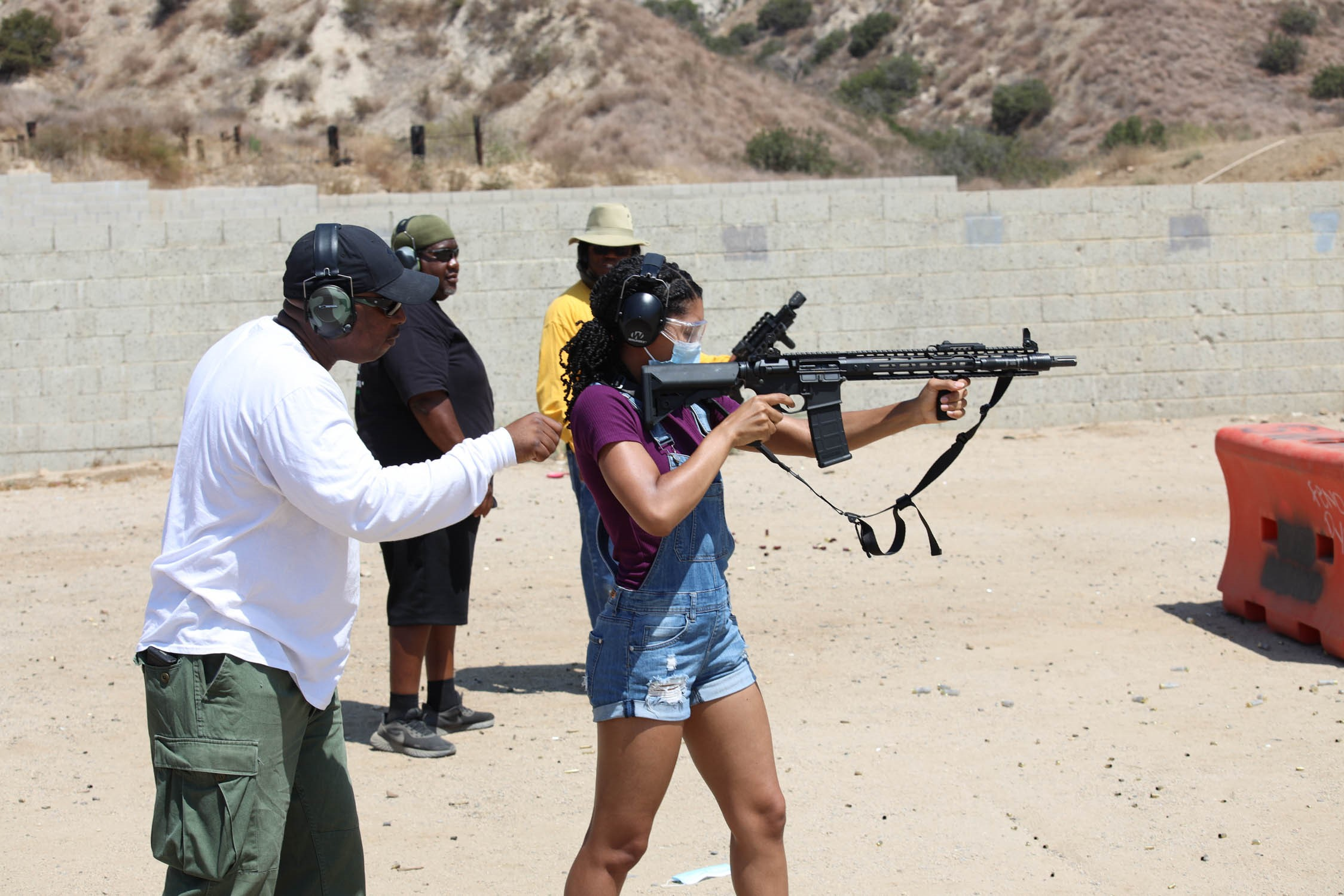 An instructor is behind a female student. The Student has a magazine fed rifle, sholdered and pointed down range.