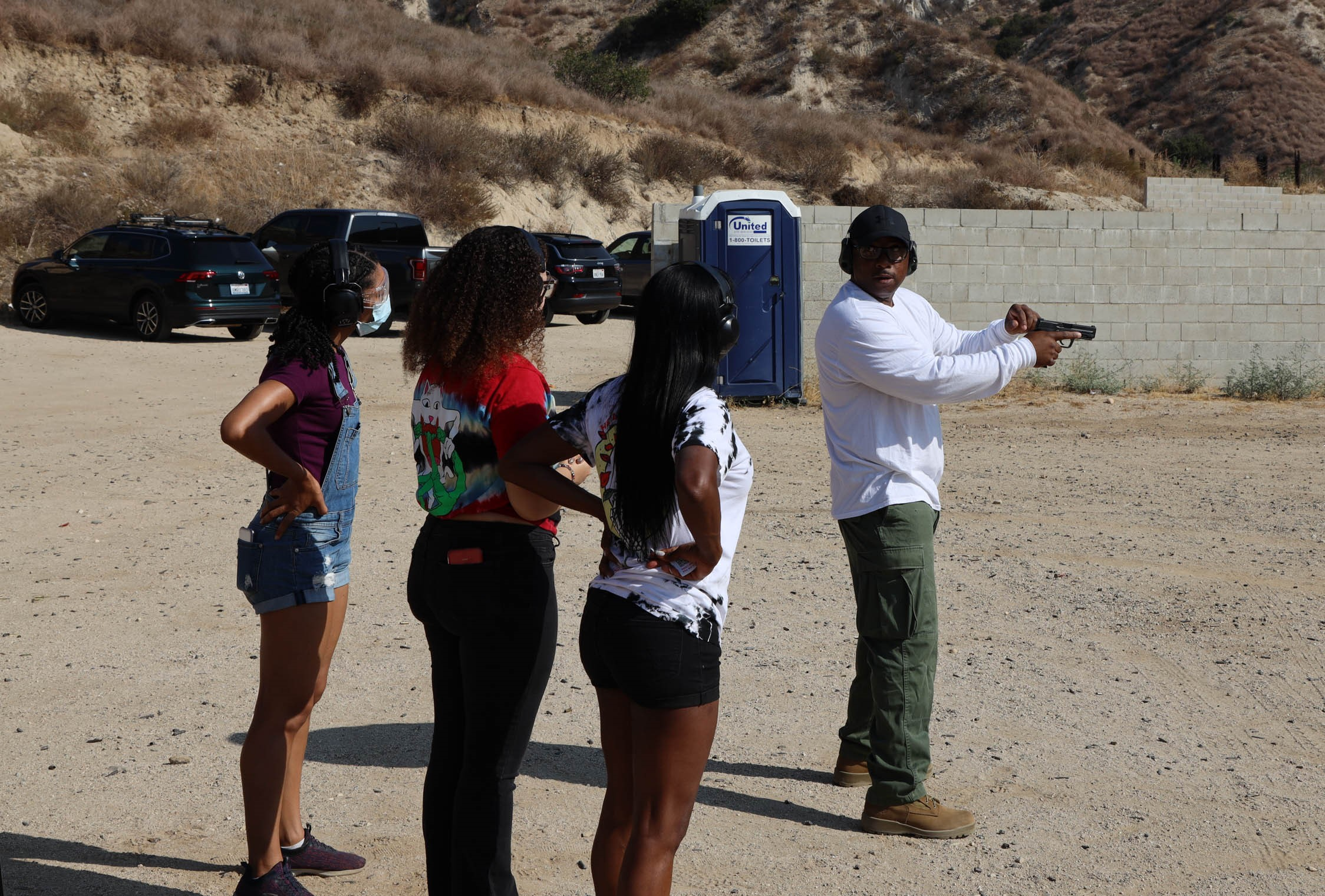Image of four people in the desert. The firearm instructor has a black hand gun pointed down rainge, he has a white shrit, ball cap and hearing protection on. he has his face turned towards three women who are behind him, the woment are watching and listening to him.