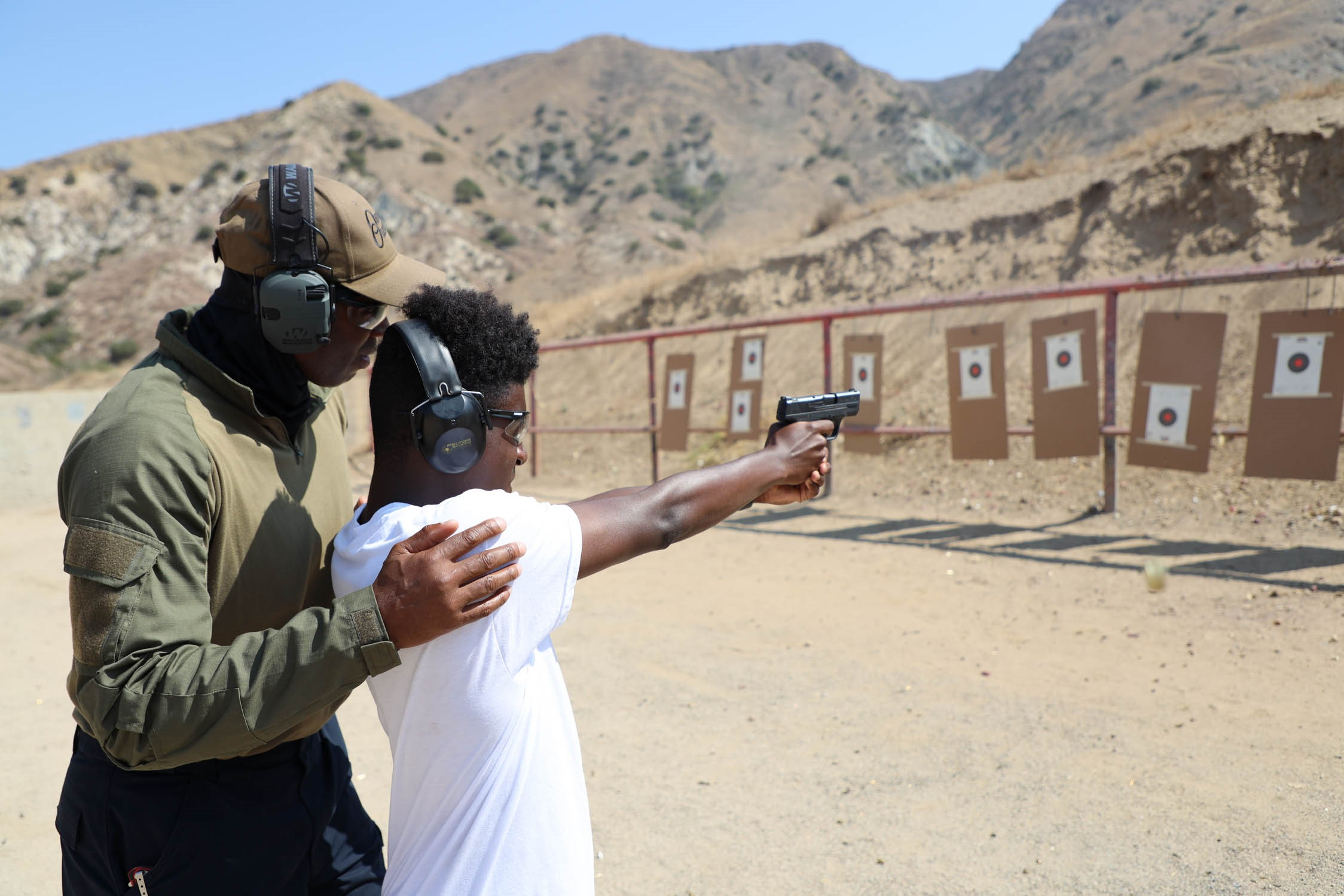 An instructor is watching over a student. The student has on large ear protectors and has a black handgun pointed at posted targets 20 feet away. the instructor is behind him with his hand on the studet's shoulder.